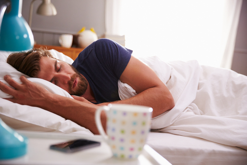 male-sleeping-with-cup-in-forefront